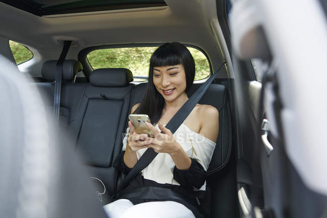Young woman in the back seat of a car using her mobile phone — Stock Photo