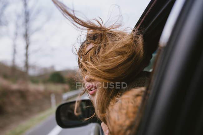 Молодая женщина, вглядываясь в окно, как автомобиль путешествия — стоковое фото
