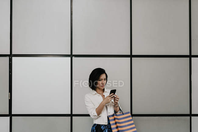Young casual asian woman using smart at shopping mall — Stock Photo