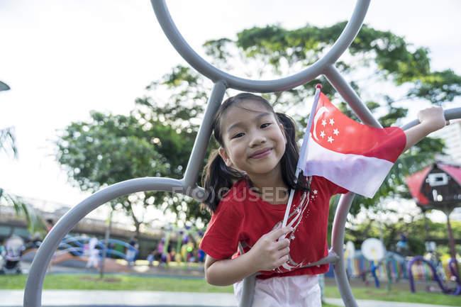 Ritratto di bambino orgoglioso Singaporean con la bandiera nazionale — Foto stock