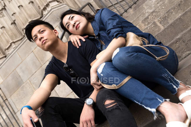 Beautiful young asian couple sitting on steps — Stock Photo