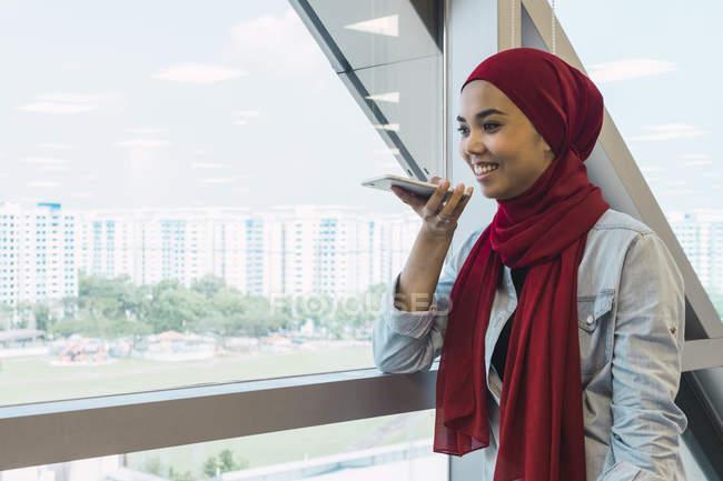 Donna giovane asiatica di affari ne su smartphone in ufficio moderno — Foto stock