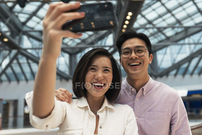Joven casual asiático pareja tomando selfie en centro comercial - foto de stock