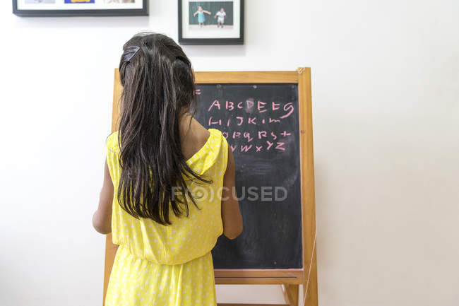 Vista traseira do jovem escrevendo na lousa — Fotografia de Stock