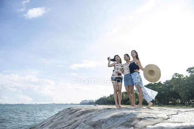 Three young ladies enjoying the breeze. — Stock Photo