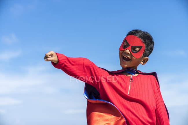 Superhéroe niño contra el fondo del cielo azul . - foto de stock