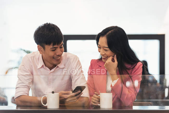 Attractive young asian couple sharing coffee and smartphone — Stock Photo