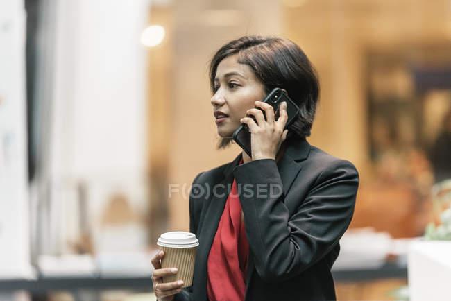 Junge asiatische Geschäftsfrau mit Kaffee und Smartphone im modernen Büro — Stockfoto