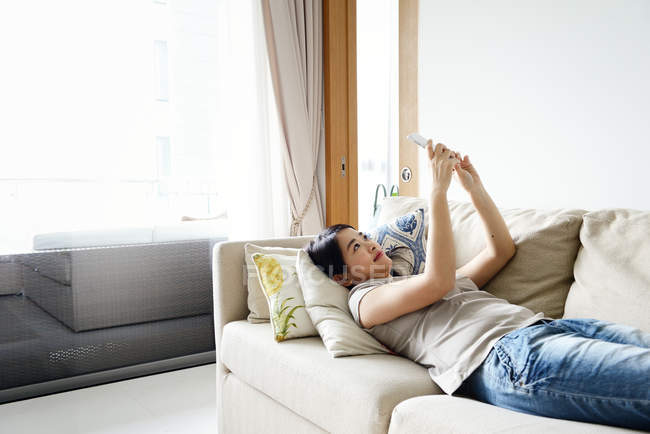 Young casual asian woman using smartphone at home — Stock Photo