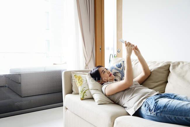 Молодая случайная азиатская женщина, использующая смартфон дома — стоковое фото