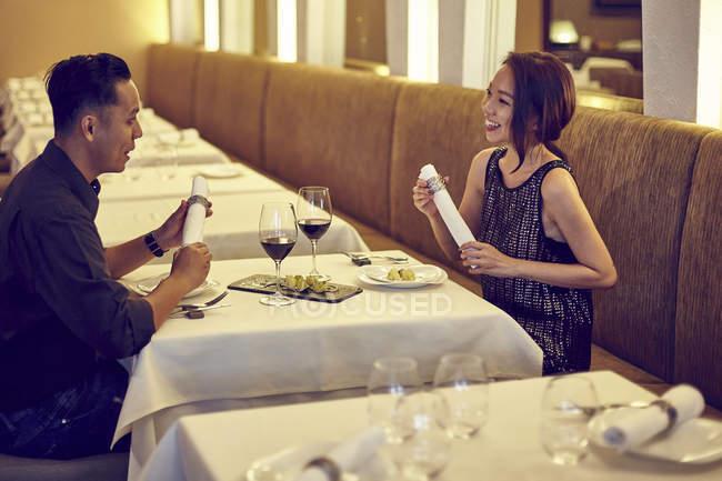 Jeune couple asiatique parlant au restaurant — Photo de stock