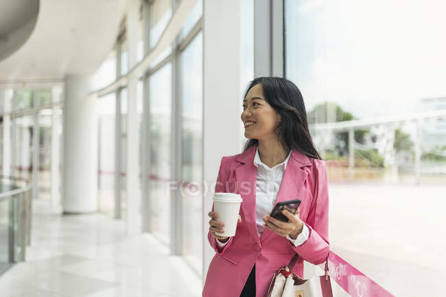 Attractive young asian woman drinking coffee and using smartphone — Stock Photo