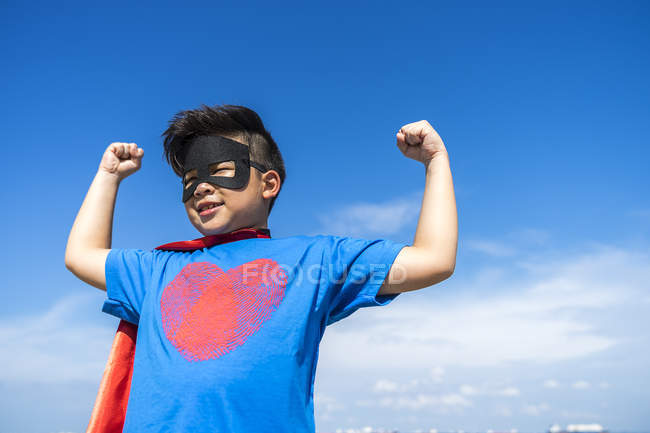 Superhero kid flexing his muscles against blue sky — Stock Photo