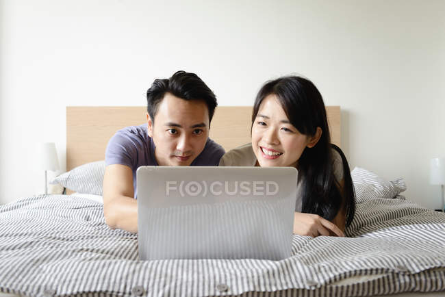 Mature asiatique casual couple à l'aide de portable dans lit — Photo de stock