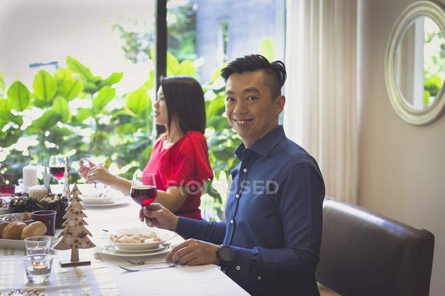 Woman wearing an elegant red dress enjoys a festive dinner with her husband in their house in Singapore. — Stock Photo