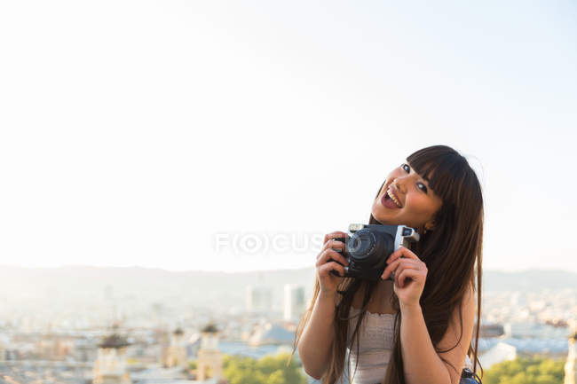 Jovem mulher euroasiática bonita posando com câmera em Barcelona — Fotografia de Stock