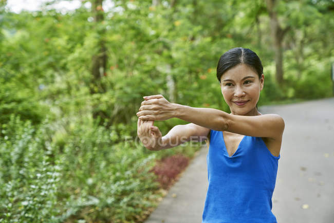 Femme d'âge mûr échauffement avant son départ dans les jardins botaniques — Photo de stock