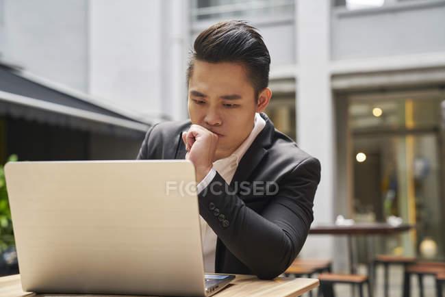 Молодой азиатский успешный бизнесмен с помощью ноутбука — стоковое фото
