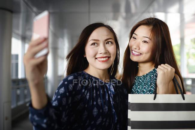 Felice bella donna asiatica a fare shopping prendendo selfie — Foto stock