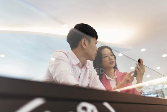 Привлекательные молодые Азиатская пара обмена смартфон — стоковое фото