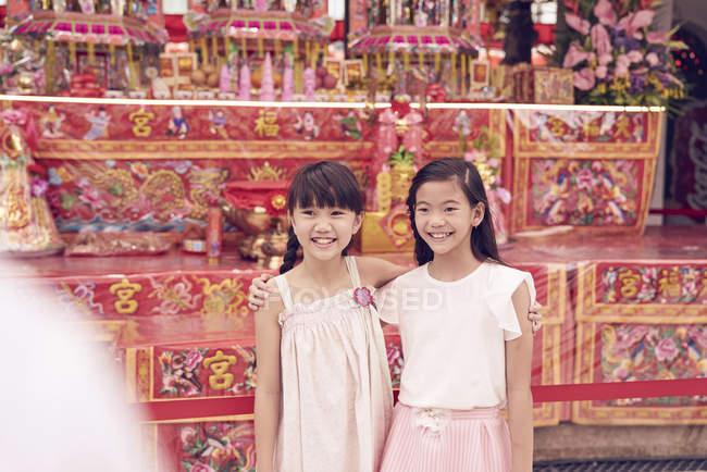 Jeune heureux asiatique famille, deux sœurs posant contre sanctuaire — Photo de stock