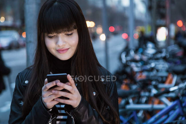 Pretty Eurasian woman looking at her phone — стоковое фото