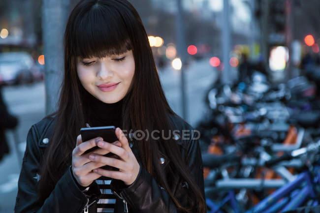 Красивая евразийская женщина смотрит на свой телефон — стоковое фото