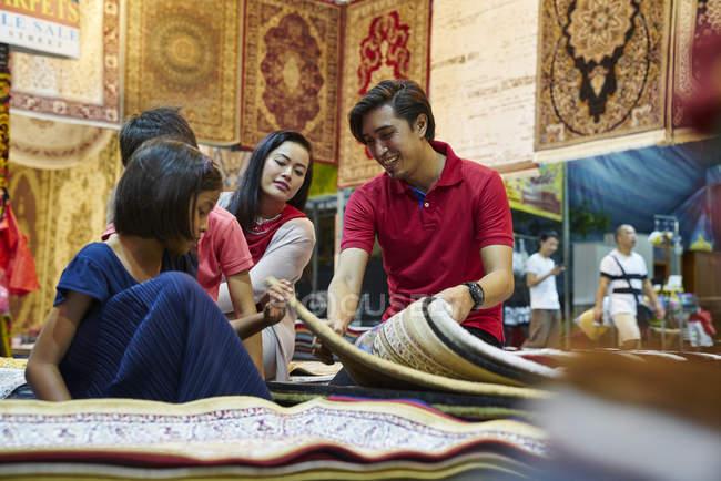 Jeune famille de navigation pour les tapis à Geylang Bazar, Singapour — Photo de stock