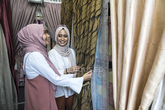 Two muslim ladies shopping for curtains. — Stock Photo