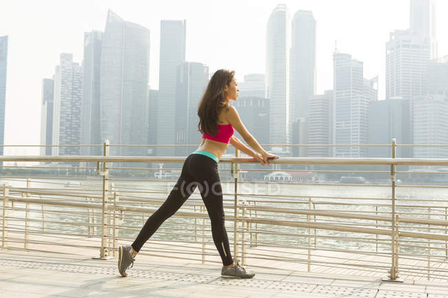 A young asian woman is stretching before her run in the Marina Bay area. — Stock Photo