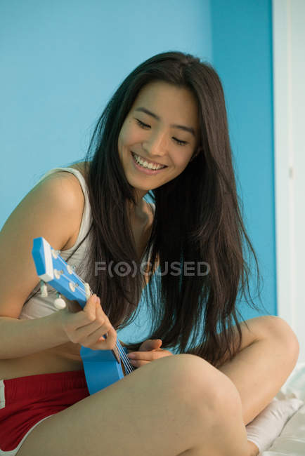 Attractive young chinese woman with playing Ukulele — Stock Photo