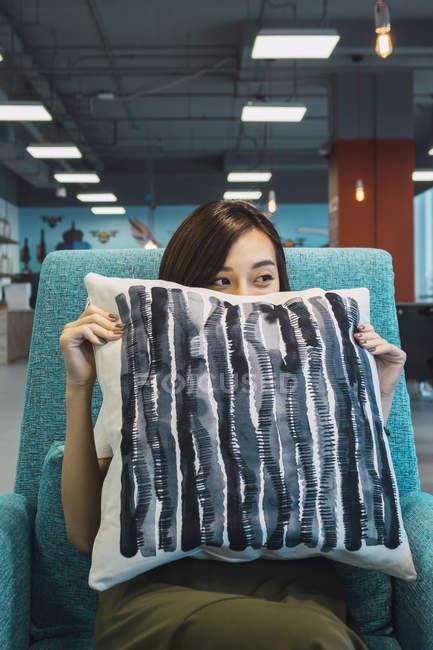 Молоді азіатські бізнес Жінка тримає подушку в сучасні офісні — стокове фото