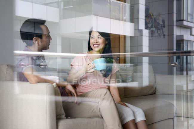 Зрелая азиатская случайная пара, сидящая с кофе дома — стоковое фото