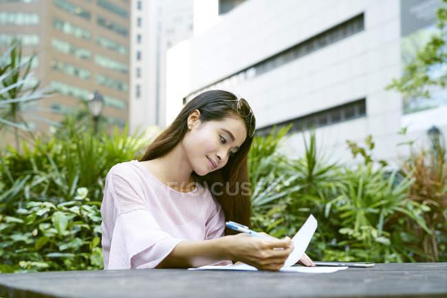 Mujer malaya alegre escribiendo felizmente en documentos al aire libre - foto de stock