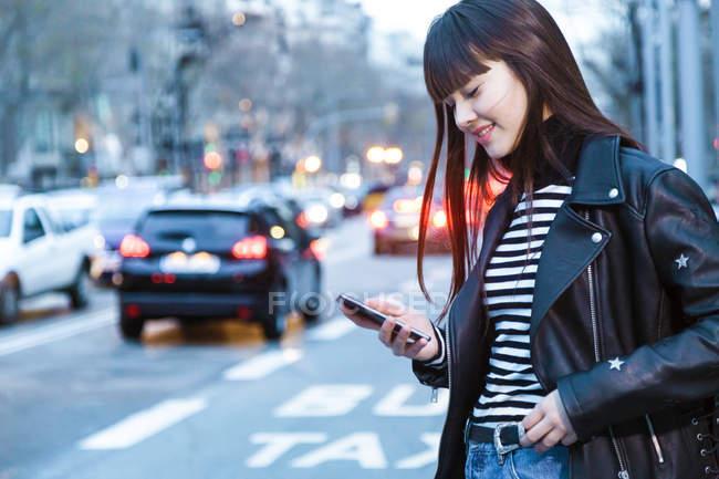 Красивая женщина смотрит на смартфон — стоковое фото