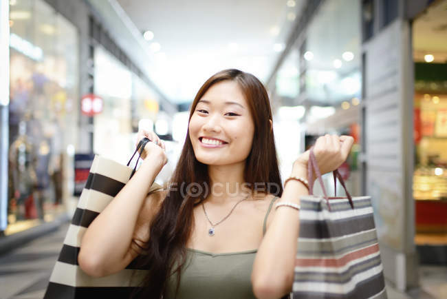 Young asian woman in shopping mall holding bags — Stock Photo