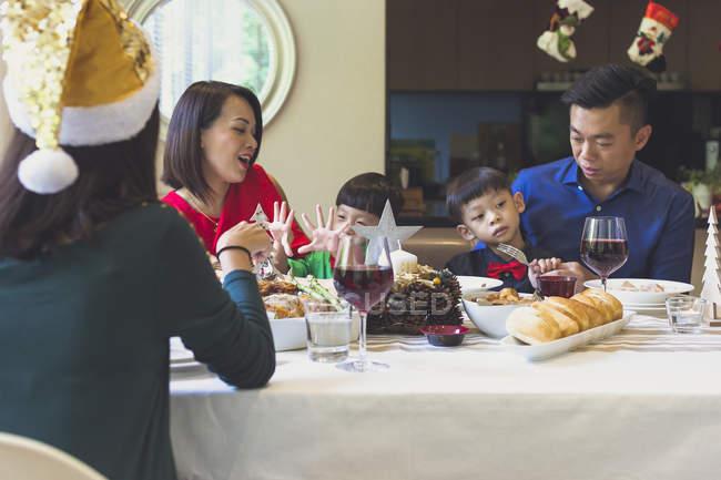 Familia de cuatro disfruta de una cena festiva con un amigo durante las vacaciones de Navidad - foto de stock