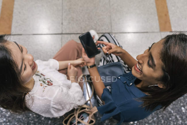 Young casual asian girls sharing smartphone — Stock Photo