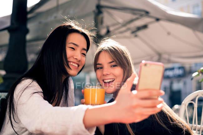 Два красивих жінок, що приймають selfie в кафе — стокове фото