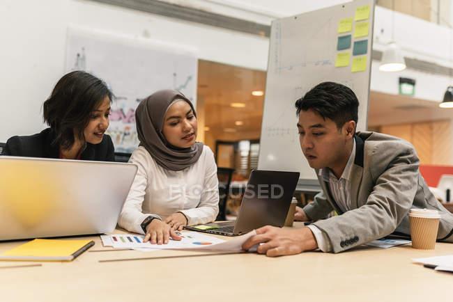 Молодые мультикультурные бизнесмены, работающие с цифровыми устройствами в современном офисе — стоковое фото