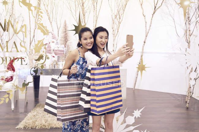 Два азіатських брюнетки покупками разом в торговий центр і беручи selfie — стокове фото