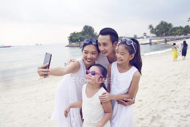 Feliz asiático familia pasando tiempo juntos en playa y tomando selfie - foto de stock