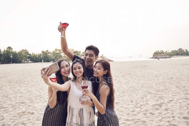 Счастливые друзья делают селфи на пляже вместе — стоковое фото