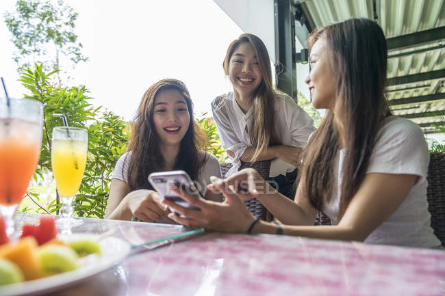 Three asian girls looking at the smartphone together in cafe — Stock Photo