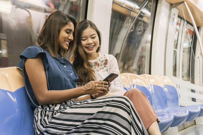 Young casual asian girls sharing smartphone it train — Stock Photo
