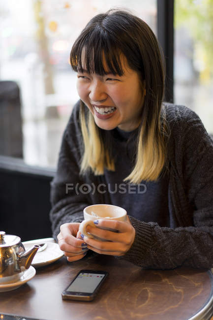 Young attractive casual asian woman with smartphone and coffee in cafe — Stock Photo