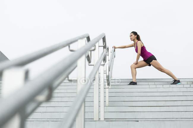 Молоді азіатські жінки тягнуться на сходах поза перед її run. — стокове фото