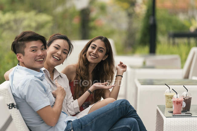 Group of friends at a restaurant, smiling at camera — Stock Photo