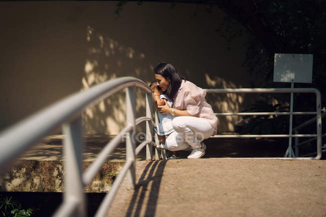 Cute asian mother and daughter looking out of railing in park — Stock Photo