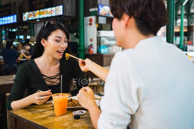 Junge asiatische paar Teilen Essen im café — Stockfoto